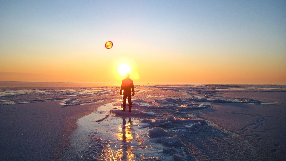 With the sun setting over the Baltic Sea Coast in Estonia, a figure stands on the frozen lake looking to the horizon.