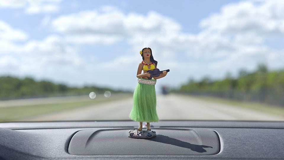 Hula dancer on the dashboard with the open road